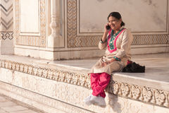Traditionally dressed Indian woman chatting happily bright morning taj-mahal. Dressed in the traditional indian pantsuit 'salwar kameez' an Indian woman is seen Stock Photo