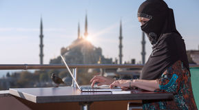 Traditionally dressed Muslim Woman working on computer Stock Images