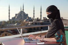 Traditionally dressed Muslim Woman working on computer Royalty Free Stock Images