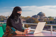 Traditionally dressed Muslim Woman working on computer Royalty Free Stock Image