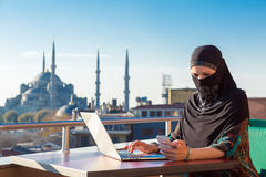 Traditionally dressed Muslim Woman working on computer Royalty Free Stock Photo