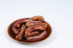 Traditionally grilled sausages on a plate. Plenty grilled sausages on plate isolated Stock Images