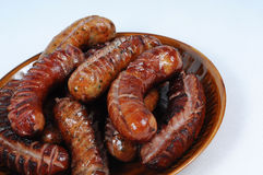 Traditionally grilled sausages on a plate. Plenty grilled sausages on plate isolated Stock Image