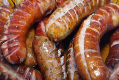 Traditionally grilled sausages on a plate. Plenty grilled sausages on plate isolated Royalty Free Stock Image