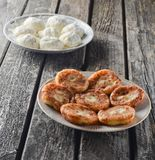 Traditionally, Russian raw and fried pancakes with cottage cheese. Cheesecakes on a wooden rustic table. The cooking process Royalty Free Stock Image