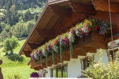 Traditioneel die chalet met de tijd van de bloemenzomer wordt verfraaid stock foto's