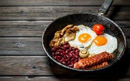 Traditioneel Engels Ontbijt met gebraden eieren, worsten en bonen stock foto's