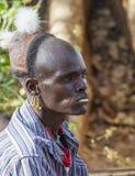Traditioneel geklede Hamar-mens met het kauwen van stok in zijn mond Turmi, Omo-Vallei, Ethiopië Stock Afbeeldingen