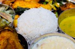 Traditioneel Indisch voedsel, Bengaalse voedselthali, rijst, dal, vissen, en groenten stock afbeeldingen