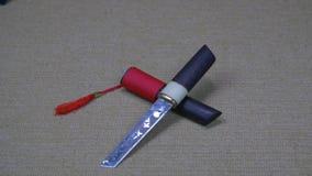Traditioneel Japans kort zwaard met rode leeswijzer die op tatamimat liggen stock videobeelden