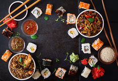 Traditioneel Japans voedsel - sushi, broodjes, rijst met garnalen en udon noedels met kip en paddestoelen op een donkere achtergr Stock Fotografie