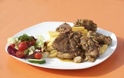 Traditioneel Maltees voedsel - konijn met verse die groenten en spaanders op oranje achtergrond worden geïsoleerd malta Fenek Royalty-vrije Stock Foto