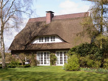 Traditioneel plattelandshuisje met met stro bedekt dak Stock Afbeeldingen