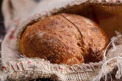 Traditioneel rogge artisanaal brood in een zak Stilleven op een houten lijst royalty-vrije stock afbeeldingen