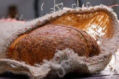 Traditioneel rond artisanaal brood in een zak Stilleven op een houten lijst royalty-vrije stock afbeeldingen