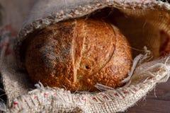 Traditioneel rond artisanaal roggebrood in een zak Stilleven op houten achtergrond stock afbeeldingen