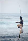 Traditioneel Sri Lanka: stelt die in oceaanbranding vissen Stock Foto