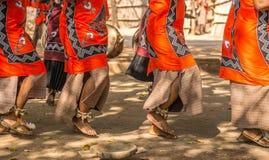 Traditionele Afrikaanse dansers op sandalsdans in openlucht in helder gekleurde kleding stock foto