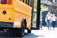 traditionele Amerikaanse schoolbus met vage groep studenten die lopen stock afbeelding