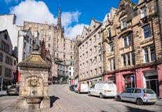 Traditionele Architectuur en Kleurrijke Winkels langs een Buigende Straat in Edinburgh en Blauwe Hemel royalty-vrije stock fotografie