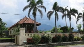 Traditionele architectuur op het eiland van Bali in Indonesië Weergeven van een huis met een tuin met tropische vegetatie en palm royalty-vrije stock foto's
