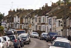 Traditionele Britse die huizen op een rij met auto op de straat wordt geparkeerd stock fotografie