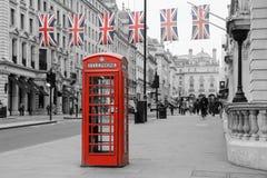 Traditionele Britse rode telefooncel met vlaggen royalty-vrije stock foto