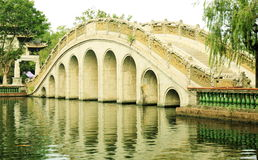 Traditionele Chinese boogbrug in oude Chinese tuin, Aziatische klassieke boogbrug in China Stock Afbeeldingen