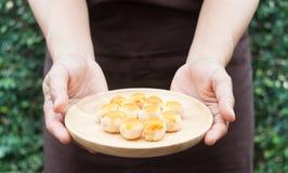 Traditionele Chinese gele minicakes op hand van bakker Stock Fotografie