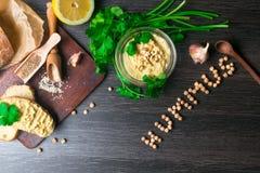 Traditionele die Hummus of houmous, voorgerecht van fijngestampte kekers met tahini, sukade, knoflook wordt gemaakt, olijfolie, p stock fotografie
