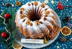 Traditionele die vruchtencake voor Kerstmis met gepoederde suiker en noten, rozijnen wordt verfraaid stock foto's