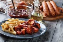 Traditionele Duitse currywurst - stukken van worst met kerriesaus stock fotografie