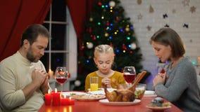 Traditionele familie die vóór het hebben van Kerstmisdiner bidden, geloof in godschristendom stock footage