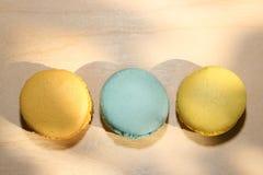 Traditionele Franse gele en blauwe macarons met zonschaduwen op houten achtergrond Stock Fotografie