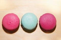Traditionele Franse roze en blauwe macarons met zonschaduwen op houten achtergrond Royalty-vrije Stock Afbeelding