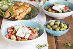 Traditionele Griekse lunch: salade met feta, souvlaki, olijven en wijn royalty-vrije stock afbeeldingen
