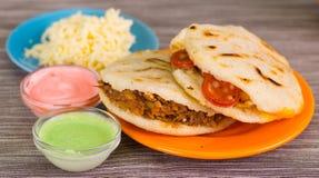 Traditionele heerlijke arepas, verscheurde kippenavocado en cheddarkaas en verscheurd rundvlees met geraspte kaas, avocado stock afbeeldingen