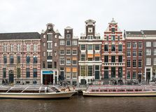 Traditionele historische Nederlandse geveltophuizen naast kanaal in Amsterdam stock afbeelding