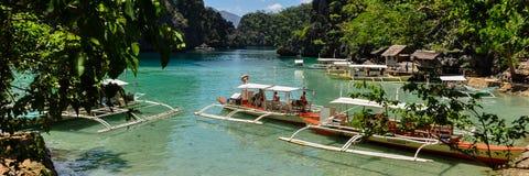 Traditionele houten Filipijnse boten in een blauwe lagune Stock Foto's