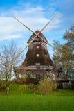 Traditionele houten windmolen in een weelderige tuin Stock Afbeeldingen