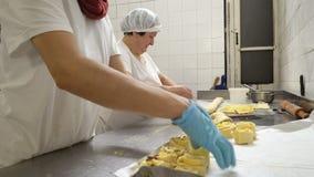 Traditionele Italiaanse bakkerij Twee vrouwelijke bakkers bereiden zoete broodjes met room Pasticcera, rozijnen en appelen voor stock videobeelden