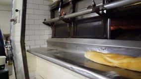 Traditionele Italiaanse familiebakkerij Een vrouwelijke bakker neemt heet brood uit de oven stock videobeelden