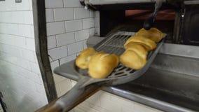 Traditionele Italiaanse familiebakkerij Een vrouwelijke bakker neemt hete broodjes uit de oven stock video