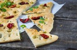 Traditionele Italiaanse focaccia met in de zon gedroogde tomaten, olijven en kruiden Royalty-vrije Stock Afbeeldingen