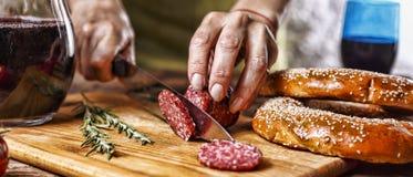 Traditionele Italiaanse rode wijn, salami, rozemarijn, brood Sluit omhoog van een de besnoeiingssalami van de persoons` s hand op stock foto
