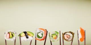Traditionele Japanse die sushistukken tussen eetstokjes worden geplaatst stock foto's