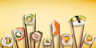 Traditionele Japanse die sushistukken tussen gescheiden eetstokjes, op pastelkleurachtergrond worden geplaatst stock foto's