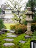 Traditionele Japanse tuin met steenlantaarn en wit kasteel stock afbeelding