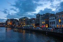 Traditionele kanaalhuizen op Damrak bij schemer in Amsterdam stock afbeelding