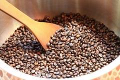 Traditionele koffiebonen die in metaalbassin roosteren met spatel Stock Foto